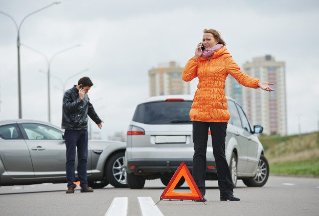 A Woman and A Man On Phones After Minor Car Accident