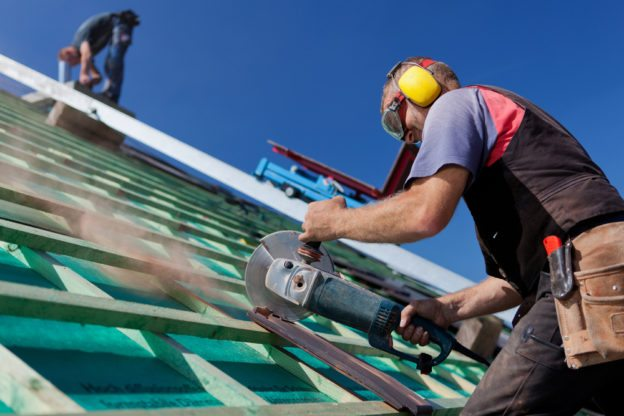 Construction Worker Using Power Saw to cut roof tiles