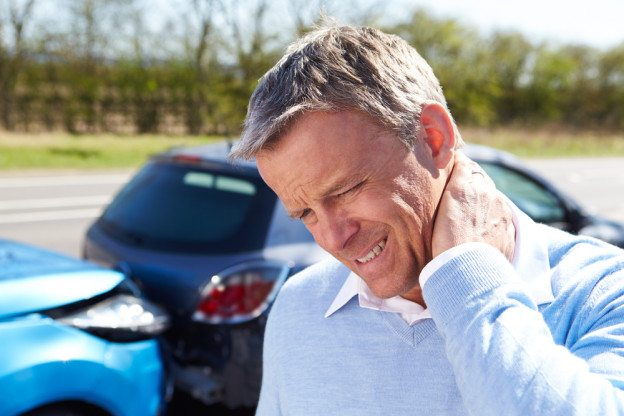 Man rubbing neck after a car accident
