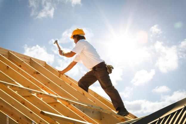 Construction worker building a home roof