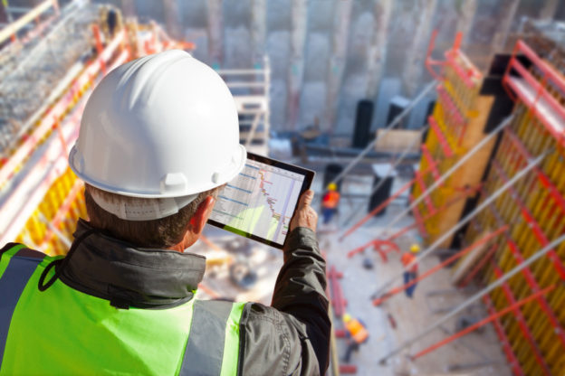 civil engineer or architect with hardhat on construction site checking safety regulations on iPad