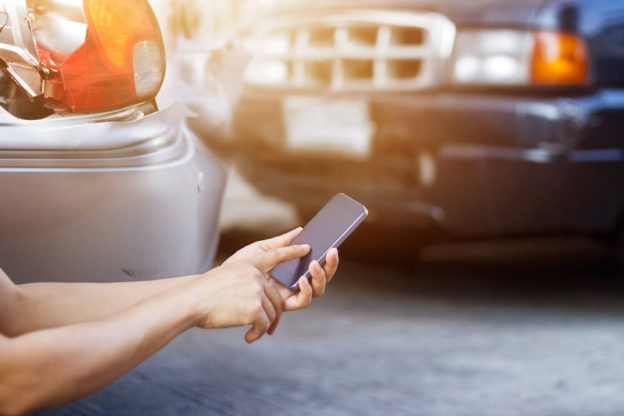 person using phone after car accident