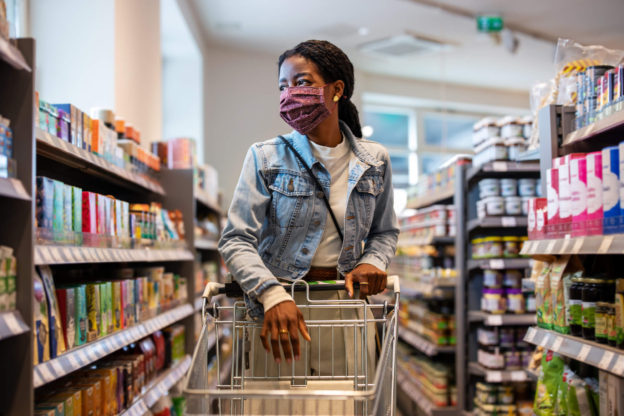 young woman shopping for groceries wearing a mask