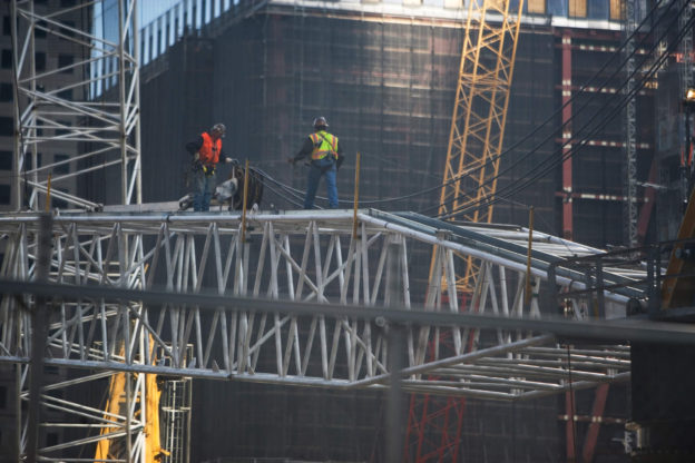 new york city construction workers high up on scaffolds