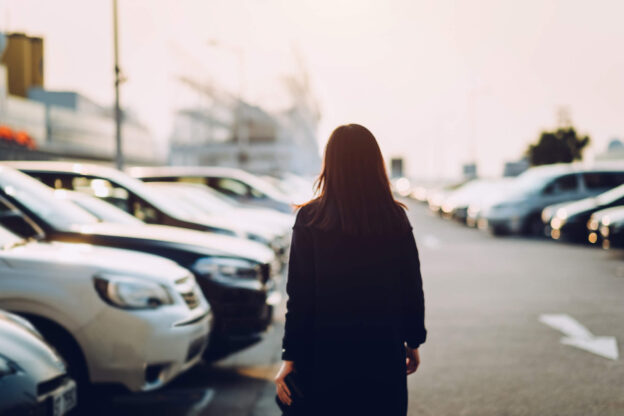 woman looking for car in parking lot
