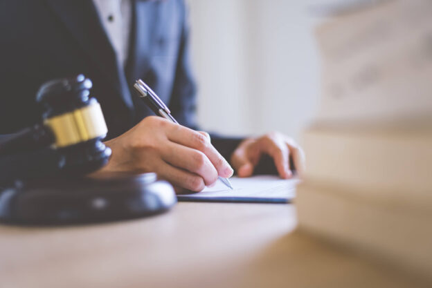 lawyer writing on paper in offfice